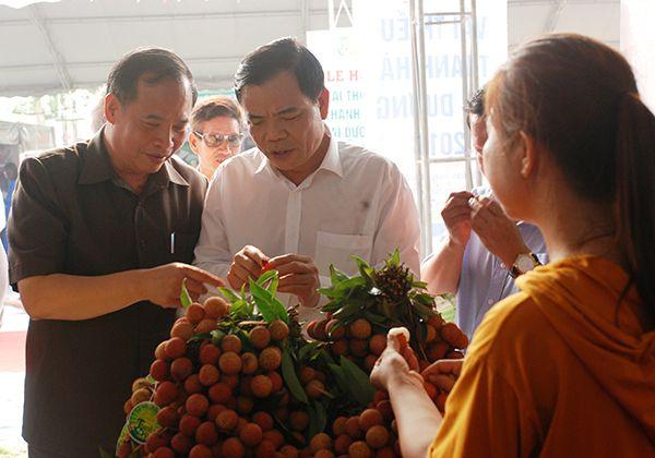 Bộ trưởng Bộ NNPTNT Ngyễn Xuân Cường và Bí thư Tỉnh ủy Hải Dương Nguyễn Mạnh Hiển nếm thử vải thiều tại các gian hàng.